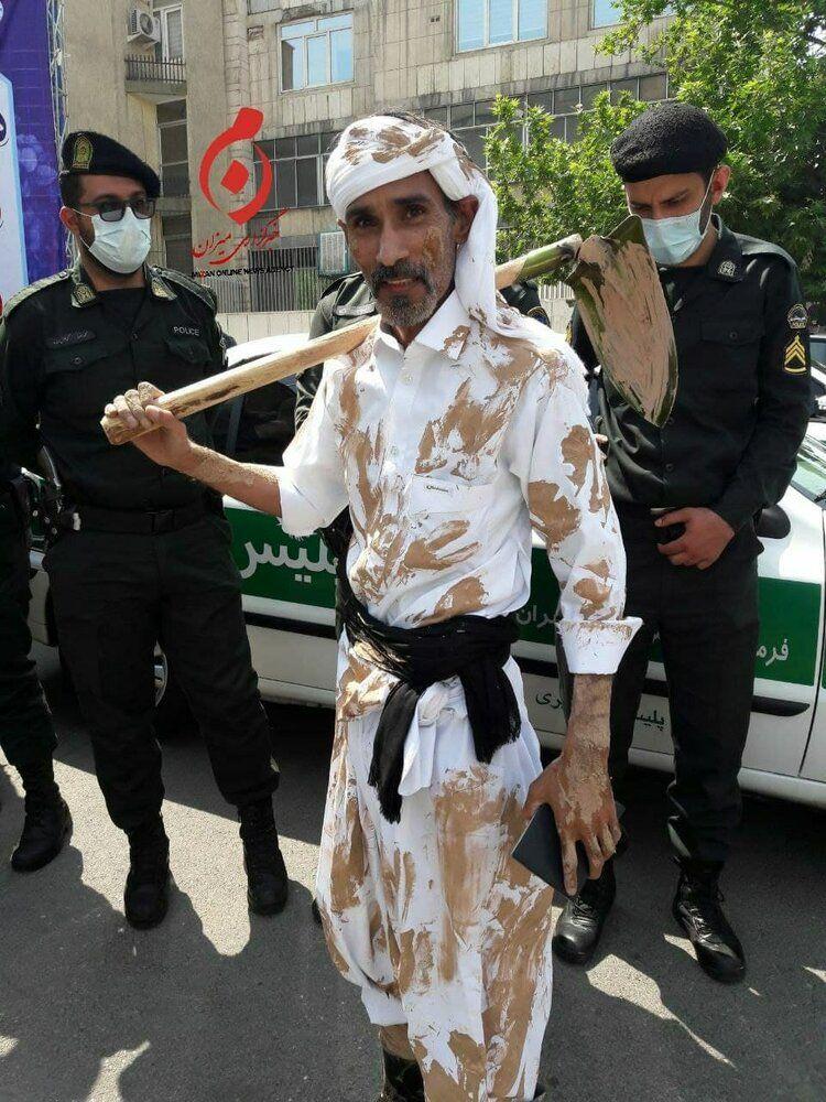 عکس   داوطلبی با کلنگ و لباسی گلی در ستاد انتخابات